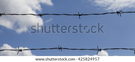 Barbed wire on the background of the cloudy sky.