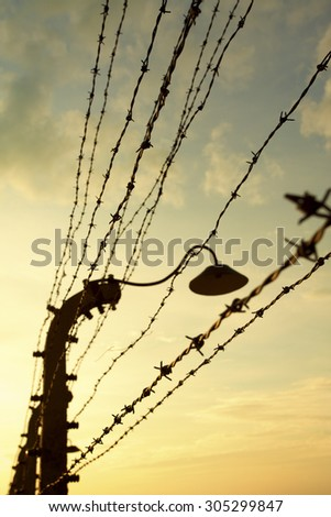Barbed wires fences on yellow sunset sky background. Poland