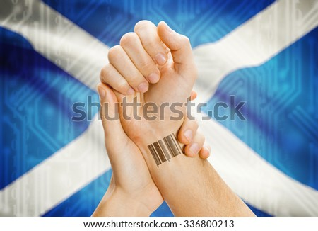 Barcode ID number on wrist of a human and national flag on background - Scotland