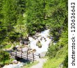 Bardonecchia area, Piemonte Region, Italian Alps. Bridge on the river in Alpine forest. - stock photo