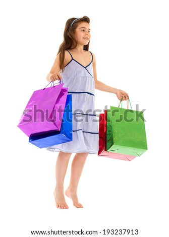 bare little brunette in a summer dress is with colorful bags in their hands on a white background