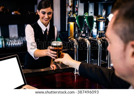 Barmaid serving a pint to customer with laptop in a bar