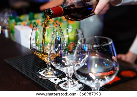 Barman pouring snifter of brandy in elegant typical cognac glass on cafe Interior background