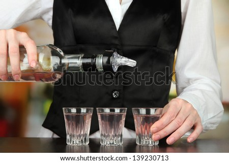 Barmen hand with bottle  pouring beverage into glasses, on bright background