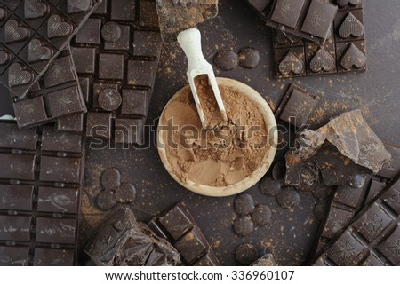 Bars, chopped and chips of  dark chocolate with cacao powder in wooden bowl