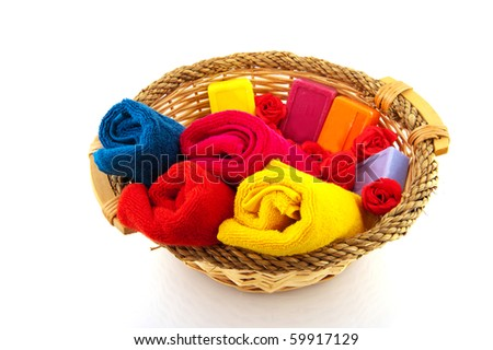 Basket with rolled towels soap and roses