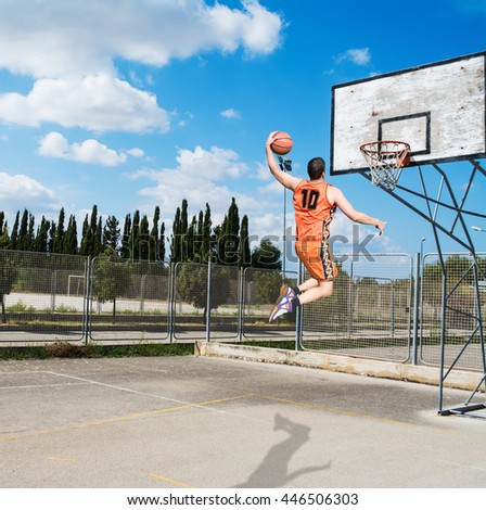 basketball player dunking in a playground