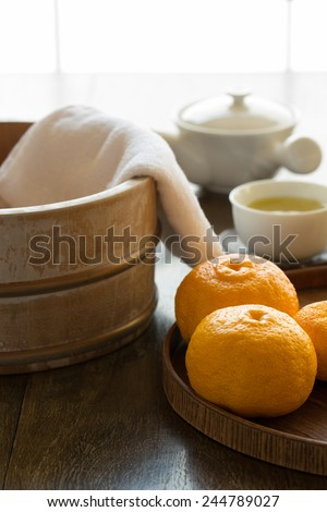 Bath bucket, towel, and fruits of yuzu in preparation to a traditional yuzu bath at onsen (yuzuyu and yuzuburo) on a day of winter solstice (old Japanese custom). Served with a cup of refreshing tea.