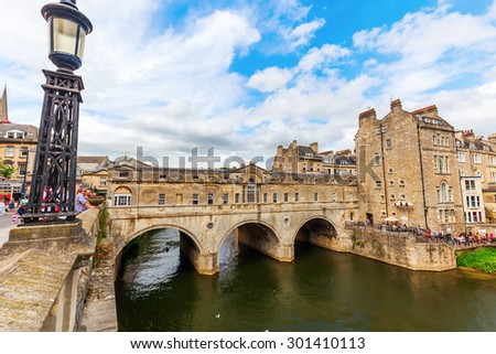 BATH, ENGLAND - JULY 04, 2015: Pulteney Bridge over the Avon in Bath with unidentified people. It was designed by Robert Adam and is exceptional in having shops built across full span on both sides.