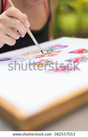 Batik process: woman artist paints on fabric, Batik-making. Artist paint the underwater creatures on a batik fabric. Selective focus, shallow depth of field. (set photo)