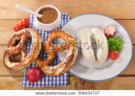 Bavarian veal sausage breakfast with two sausages, soft pretzels and mild mustard on wooden board from Germany