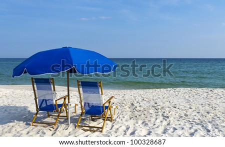 Beach chairs and an umbrella on the gulf coast.