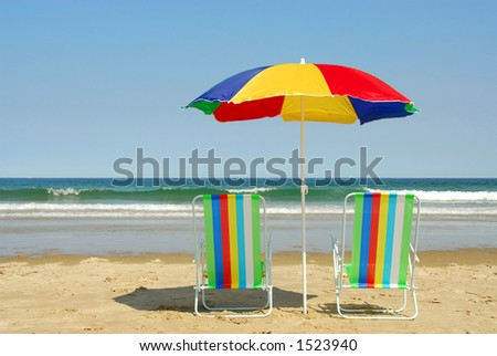 Beach chairs and umbrella on the ocean shore with surf in the background, horizontal