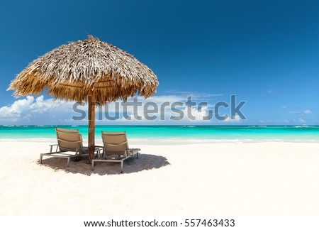 Beach chairs with umbrella and beautiful sand beach in Punta Cana, Dominican Republic