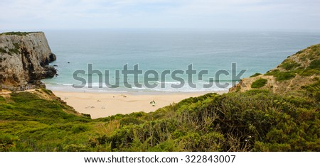 Beach in Algarve region of Portugal in cloudy day. People swimming and surfing. A view from the top