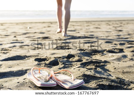 Beach Jandals/ a woman leaves her Flip-flops on the dry sand to go for a swim