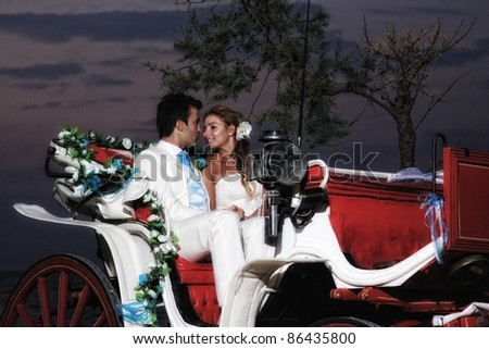 Beach wedding: bride and groom on a carriage by the sea
