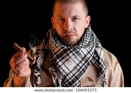 Bearded army officer wearing camo clothes and smoking cigar