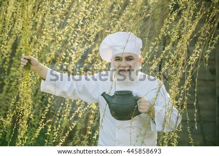bearded man cook chef in uniform and hat with long beard on smiling face holding iron old tea kettle in blooming tree branches outdoor on natural background