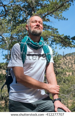 Bearded man, hiker wearing a scarf standing in the mountains, smiling and looks into the distance. Sunny day on Cyprus.