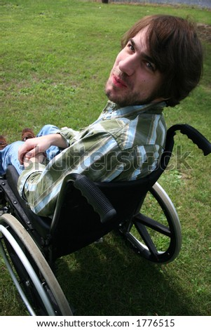 Bearded man in a wheel chair.  Has a funny expression.