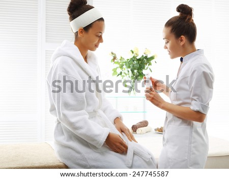 Beautician advises client the appropriate cosmetics to her skin type Two women in wellness salon dressed in white robes