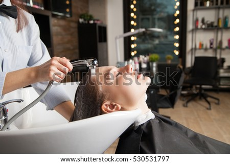 Beautician washing woman's head