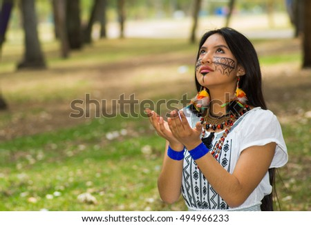 Beautiful Amazonian woman with indigenous facial paint and white traditional dress posing happily for camera in park environment, forest background