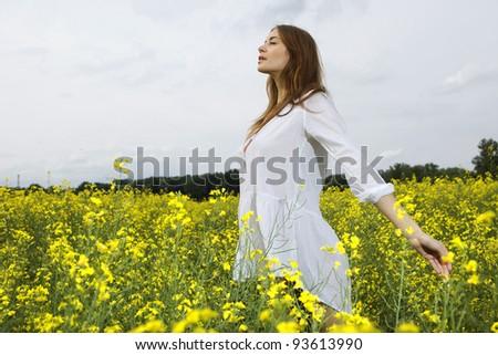 Beautiful and sensuality brunette woman in a yellow flowers field