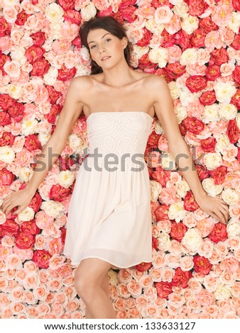 beautiful and young woman with background full of roses