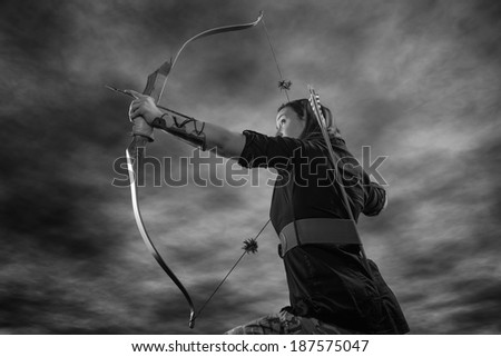Beautiful archery woman aiming, sky on background, black and white image