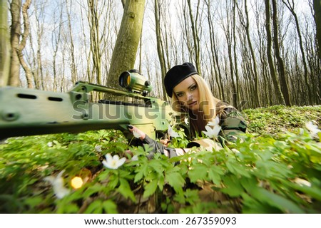 Beautiful army girl with gun  outdoor in the forest