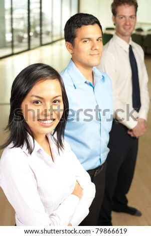 Beautiful Asian business woman and her male Hispanic and Caucasian colleagues stand behind in a row in a corporate office setting, smiling looking at camera. Vertical