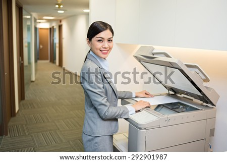 Beautiful Asian secretary using copy machine in the office