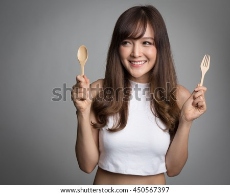 Beautiful asian woman holding spoon and fork, looking to side to copy space.