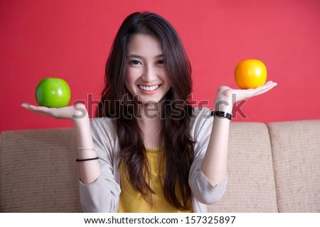 Beautiful asian woman with an orange and a green apple