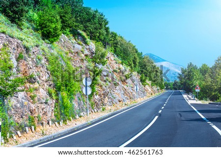 Beautiful asphalt freeway, motorway, highway without traffic through of southern landscape mountains forest during summer on a sunny day. Travel road concept.