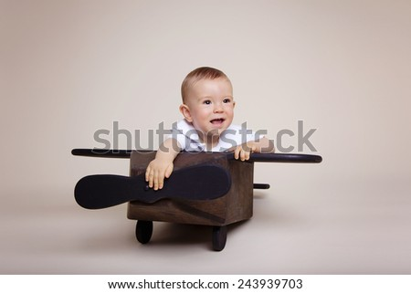 Beautiful baby boy playing inside a wooden airplane