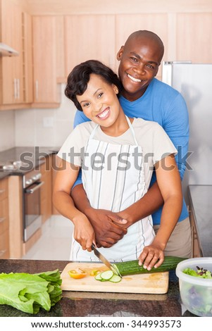 beautiful black couple cooking together in home kitchen