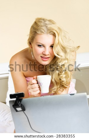 beautiful blond girl at home communicating through the Internet using a web camera