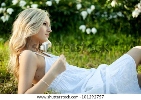 Beautiful Blond Girl with flower on grass, White Dress