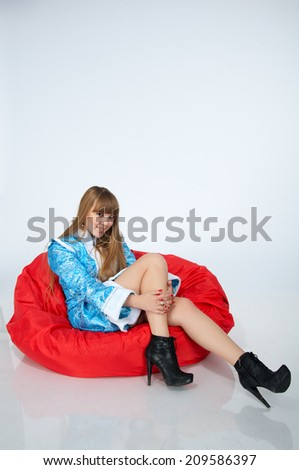 Beautiful blond snow maiden is sitting in the red chair