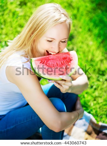 beautiful blond woman eating watermelon in the summer park