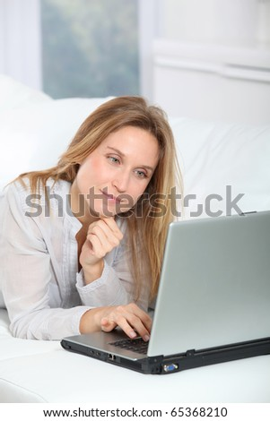Beautiful blond woman surfing on internet at home