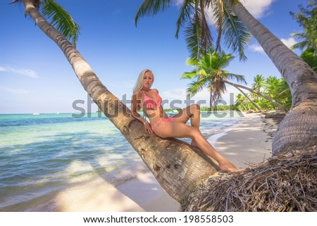 Beautiful blonde at the palm trunk at Bavaro beach in Dominican Republic Shore