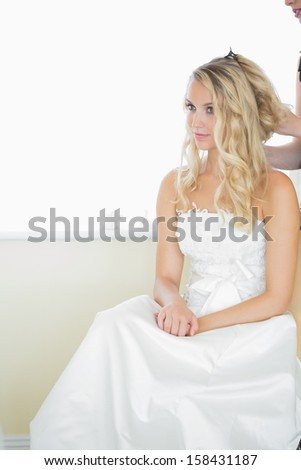 Beautiful blonde bride being prepared for the wedding wearing a wedding dress