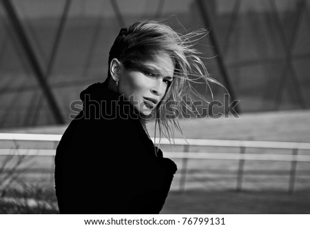 Beautiful blonde near a modern building from glass. Black-white photo.