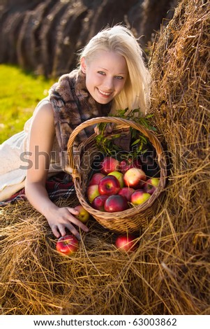beautiful blonde smiling woman with many apple in basket on haystack at farm