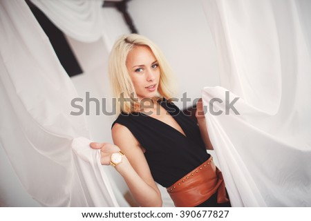 beautiful blonde woman in a black suit stands near the bed in the hotel