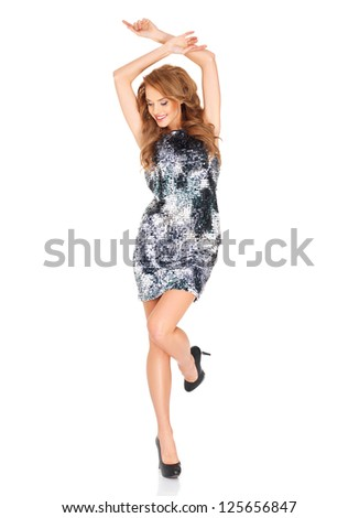 Beautiful blonde woman in a trendy dress and high heels dancing with her arms raised above her head and foot in the air isolated on white